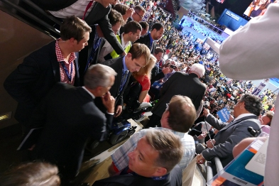 Reporters lean into the aisle to try to get a quote