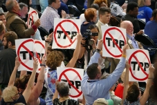 Many signs protesting the TPP supported by President Obama